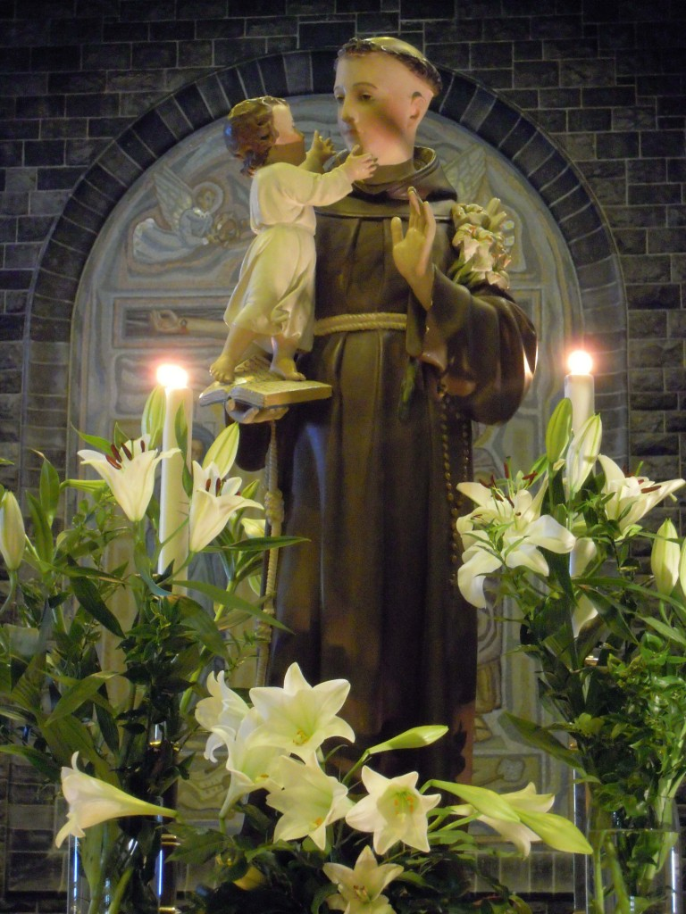 Statue of St Anthony of Padua surrounded by lilies